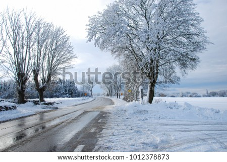 Melting snow and ice on a country road through a wintry landscape
