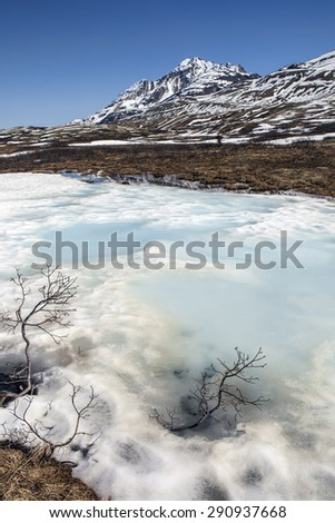 Melting snow patches in high elevation mountains in the Yukon Territory in Canada in spring. - stock photo