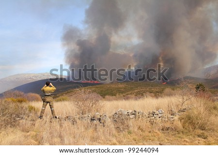 Member of the fire brigade with one focus of the burning of Corporales in the background. Cabrera Alta, Leon. - stock photo