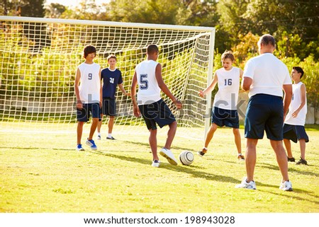 Members Of Male High School Soccer Playing Match - stock photo