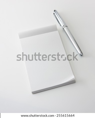 Memo pad and a silver pen, isolated on white with natural shadows. Intentionally highlighted on upper left hand corner. Focus is slightly below memopad top (where messages are likely inserted.)  - stock photo