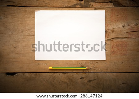 memo paper and pencil on old grungy wooden surface with dim lighting. Intentionally shot and with low key shadows - stock photo