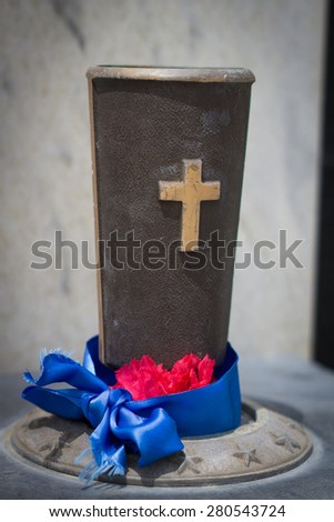 Memorial Christian grail to hold flowers at a military cemetery with ribbons. - stock photo