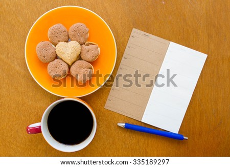 Memory blank notebook and blue pen with coffee and cookie on wooden background