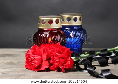 Memory lantern with candles, red carnations and ribbon on wooden table on grey background - stock photo