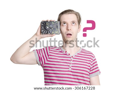 Memory loss concept, young man rolling eyes upwards and holding hard drive next to his head - stock photo
