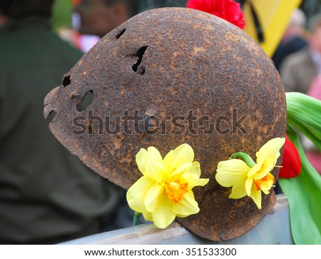 Memory of the Victory! The soldier's helmet punched by bullets decorated with flowers.