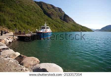 MEMURUBU, NORWAY - JULY 22, 2013: Hikers leaving boat at Memurubu Turisthytte on July 22, 2013 in Memurubu, Norway.