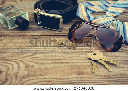 Men accessories: sunglasses, tie, cufflinks, strap, keys, perfume  on the old wood background. Toned image.  - stock photo