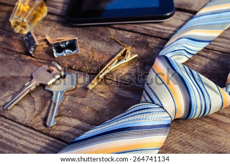 Men accessories: tie, cufflinks, tablet, perfume and keys on the old wood background. Toned image.  - stock photo
