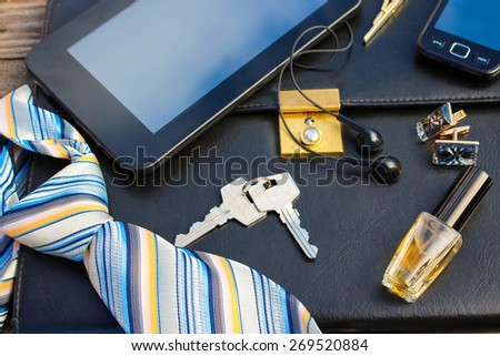 Men accessories: tie, cufflinks, tablet, perfume, mobile phone, folder of documents and keys on the old wood background.  - stock photo