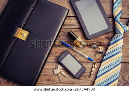 Men accessories: tie, cufflinks, tablet, perfume, pen, mobile phone, folder of documents and keys on the old wood background. Toned image. - stock photo