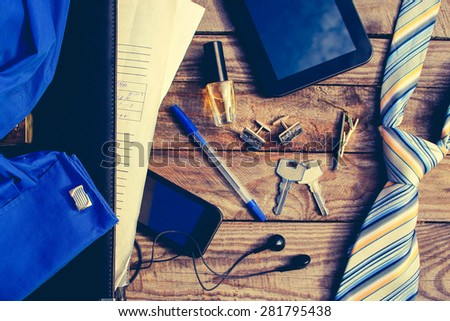 Men accessories: tie, cufflinks, tablet, perfume, pen, mobile phone, headphones, folder of documents and keys on the old wood background. On a piece of paper written digits. Toned image. - stock photo