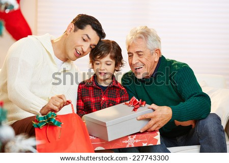 Men and child in three generations celebrating christmas with gifts - stock photo