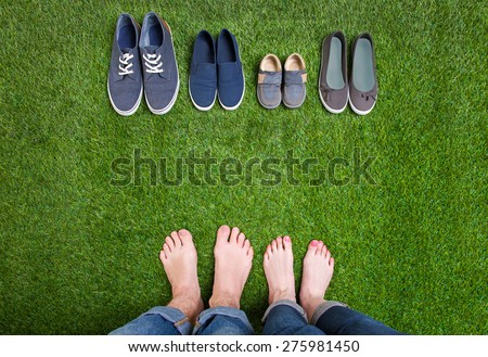 Men and woman legs with shoes standing  on grass - stock photo