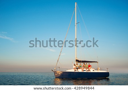 Men and women on boat. People sitting on small yacht. Edge of the world. Far away from city bustle. - stock photo