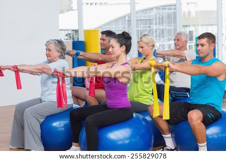 Men and women on fitness balls exercising with resistance bands in gym - stock photo
