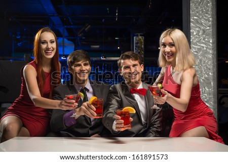 Men and women raised their glasses with cocktails in a nightclub, a party with friends
