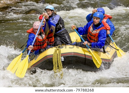Men and women whitewater rafting in Colorado. - stock photo