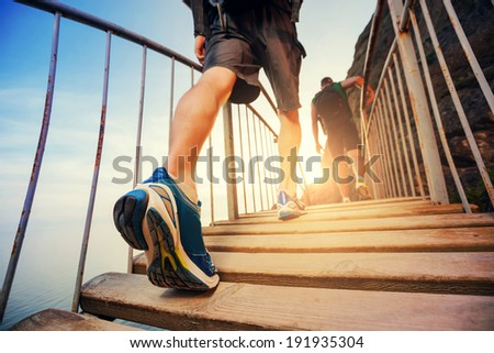 Men are hiking in the mountains, walking on a wooden bridge at sunset. Healthy lifestyle.