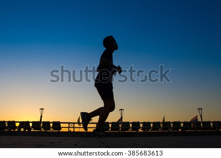 Men are silhouette jogging at a speed in the evening.