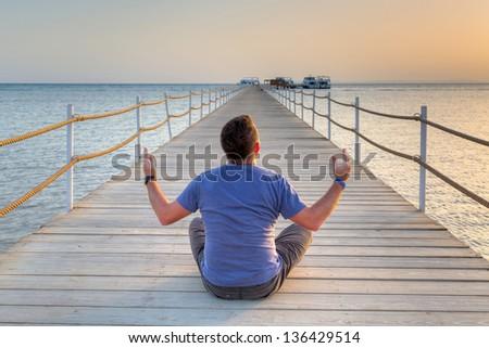 Men at meditation at the sea at sunrise - stock photo