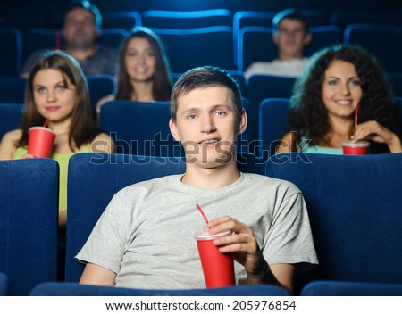 Men at the cinema. Excited young men watching movie at the cinema and drinking soda - stock photo