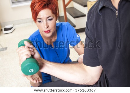 men at the physio with a dumbell