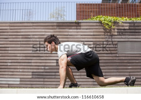Men athlete start running next to some city wall - stock photo