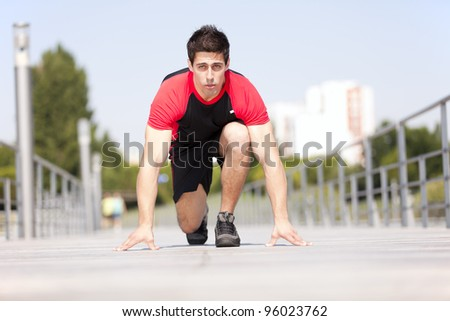 Men athlete starting running at the city park - stock photo