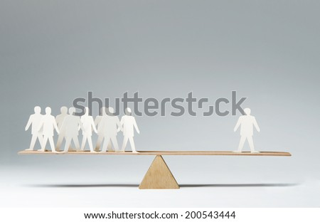 Men balanced on seesaw over a single man - stock photo