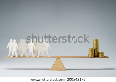 Men balanced on seesaw over a stack of coins - stock photo