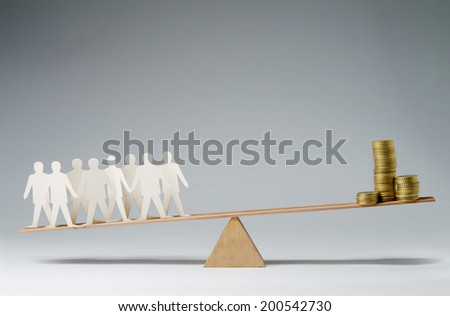 Men balanced on seesaw over a stack of coins