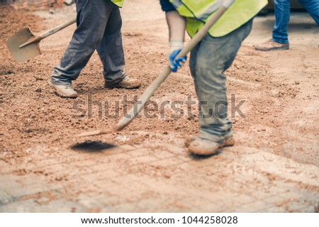Men builders with a shovel on the construction site