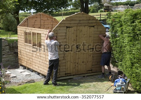 men building a wooden garden shed circa erecting a new garden shed in