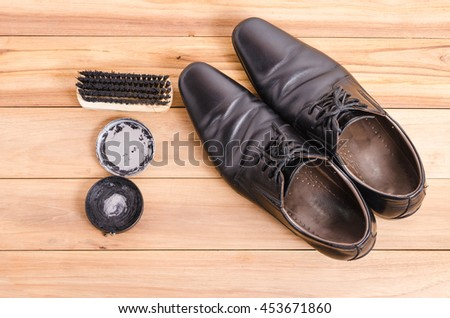 Men casual black leather shoes and polished accessories on wood - stock photo