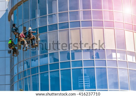 Men cleaning glass building. high-rise, industrial mountaineering