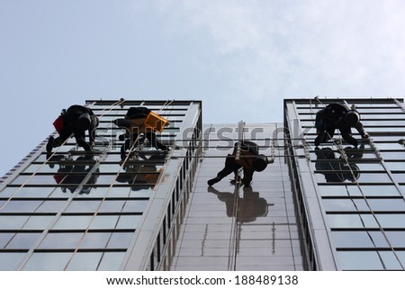 Men cleaning windows on a corporate bouilding - stock photo