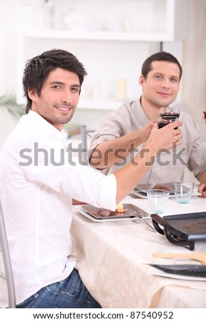 Men clinking their glasses at table - stock photo