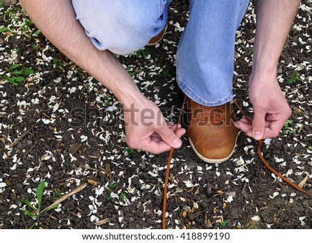 men commits an outdoor walk and stopped to tie his shoelaces on sneakers.