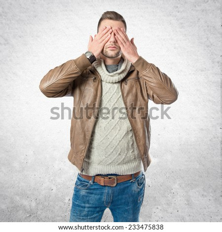Men covering his eyes over textured background