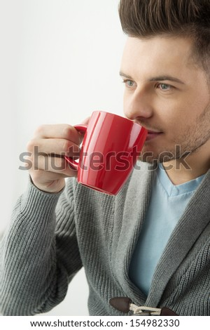 Men drinking coffee. Handsome  young men drinking coffee and looking away - stock photo