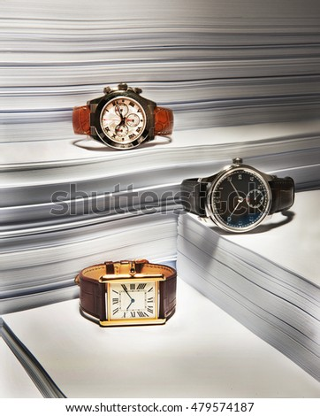 men expensive and very stylish watches on a composition with papers in background