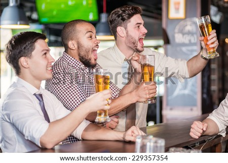 Men fans screaming and watching football on TV and drink beer. Three other men drinking beer and having fun together in the bar until the bartender standing near the rack