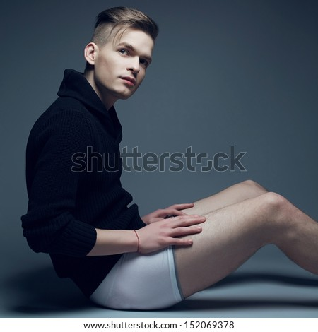 Men fashion concept. Portrait of a young fashionable man in trendy clothes and underwear sitting over gray background and holding his legs. Perfect haircut. Hipster style. Copy-space. Studio shot - stock photo