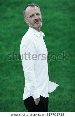 Men fashion concept. Portrait of mature charismatic man with blue eyes and beard wearing white shirt and black pants. Silver short hair. Iconic classic style. Outdoor shot