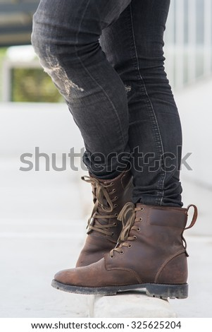 Men fashion legs in black jeans and brown leather boots on white