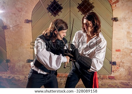 Men fighting with swords at old town street - stock photo