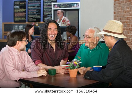 Men from various ethnic groups and ages in cafe - stock photo