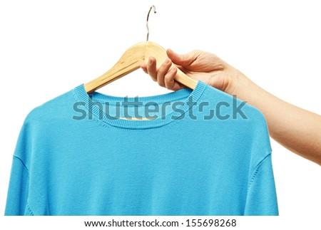 men hand holding hanger with t-shirt - stock photo